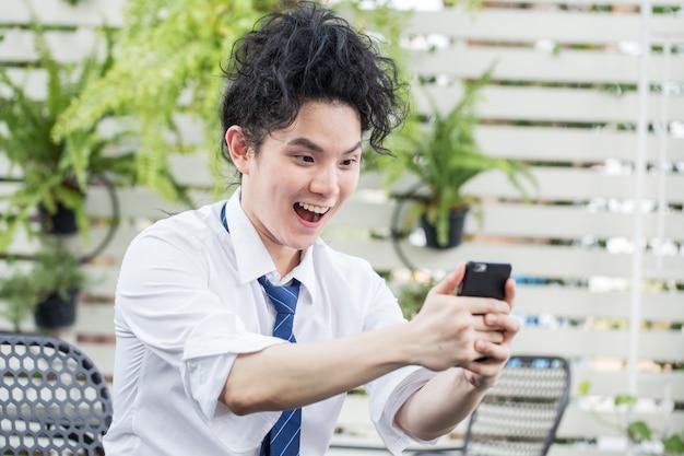 Hombre de negocios asiático joven emocionado celebrando el éxito, hombre de pelo rizado asiático manteniendo los brazos levantados mirando teléfono inteligente feliz por la victoria