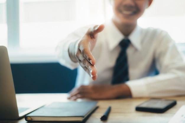 Hombre de negocios asiático joven que extiende su brazo en un apretón de manos.