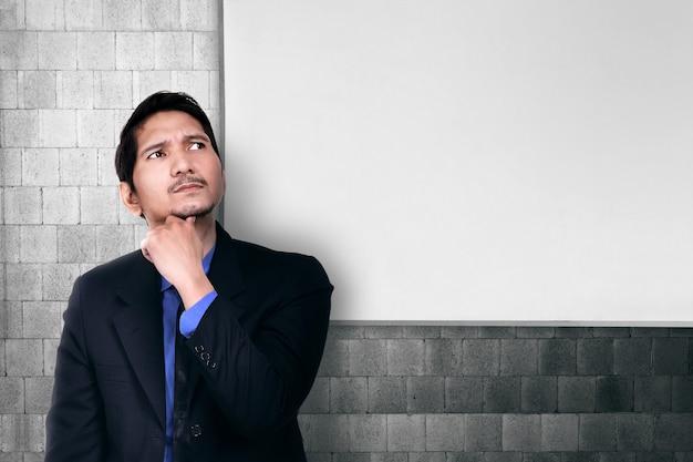 Hombre de negocios asiático joven que piensa para la solución
