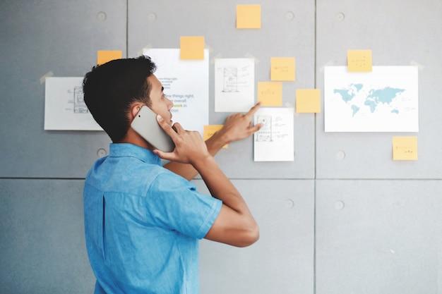 Hombre de negocios asiático joven que trabaja en la sala de reunión de la oficina y que habla vía smartphone