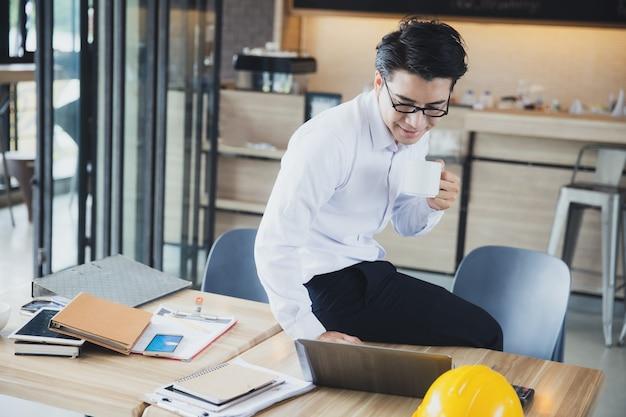 Hombre de negocios asiático joven trabaja desde casa durante relajarse bebiendo una taza de café y mirando portátil