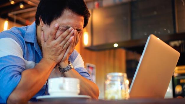 Hombre de negocios asiático en el juego casual que trabaja cabeza en la acción de la mano con la emoción de la tensión
