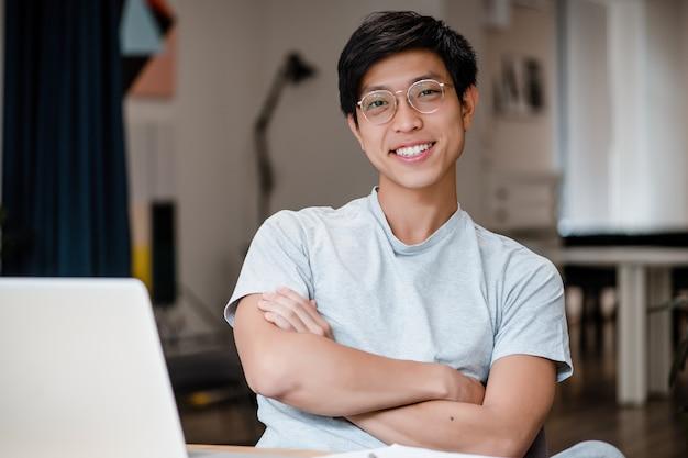 Hombre de negocios asiático milenario sonriente en la oficina de la compañía
