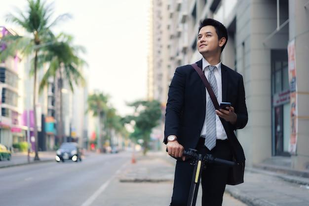 Hombre de negocios asiático está montando un scooter eléctrico y usa su teléfono móvil