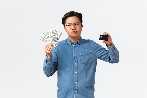 Hombre de negocios asiático perplejo en vasos con efectivo y dinero mirando dudoso en el uso de pensamiento de dinero ...
