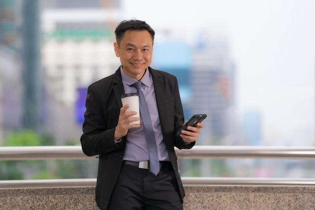 Hombre de negocios asiático que coloca y que sostiene el teléfono móvil con los edificios de oficinas de negocios en la ciudad
