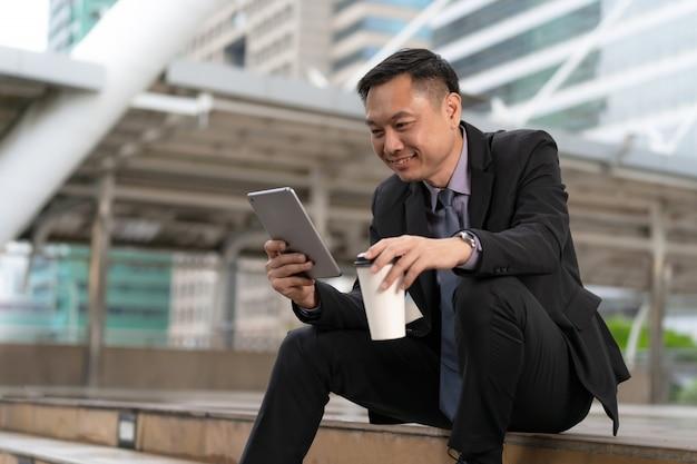 Hombre de negocios asiático que sienta y que sostiene la tableta digital con los edificios de oficinas de negocios en la ciudad