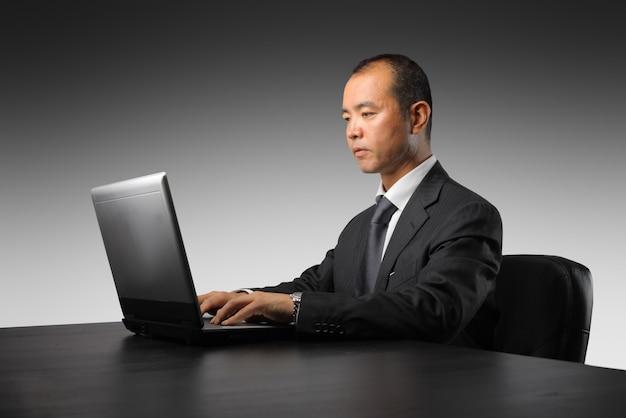 Hombre de negocios asiático que trabaja en una computadora portátil