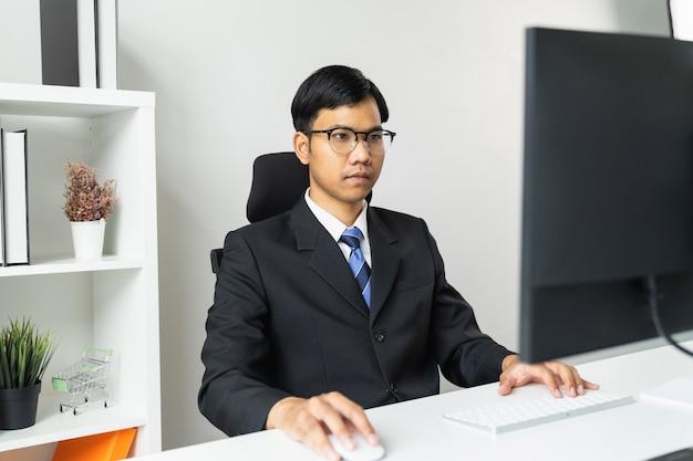 Hombre de negocios asiático que usa la computadora en la tabla en oficina.