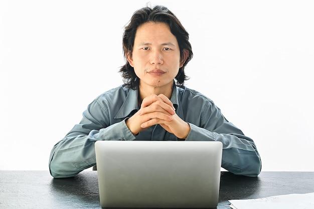 Hombre de negocios asiático que usa mirada de la computadora portátil en la cámara en blanco