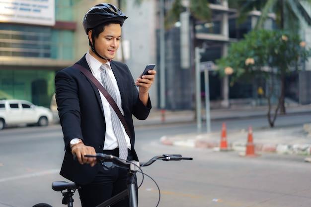 Hombre de negocios asiático que usa sus teléfonos móviles para ver aplicaciones, mapas, direcciones para trabajar por la mañana.