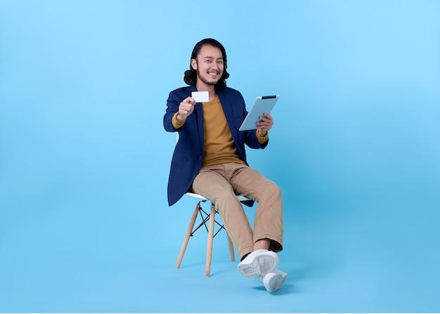Hombre de negocios asiático sonriendo feliz mostrando tarjeta de crédito y usando una tableta digital mientras está sentado en una silla en azul brillante.
