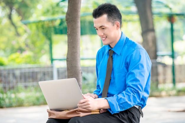 Hombre de negocios asiático sonriente que se sienta y que trabaja con la computadora portátil