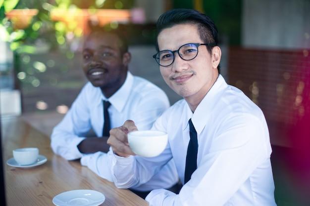 Hombre de negocios asiático de la sonrisa que sostiene una taza de café con sus amigos africanos.