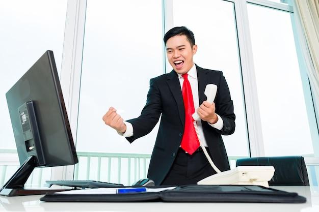 Hombre de negocios asiático telefoneando en la oficina controlando los beneficios