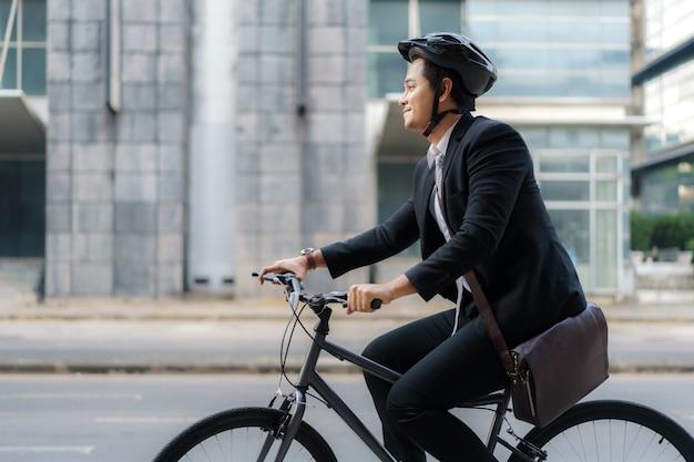 Hombre de negocios asiático en traje está montando una bicicleta en las calles de la ciudad