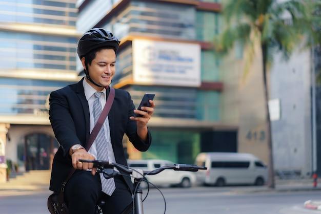 Hombre de negocios asiático usando sus teléfonos móviles para ver aplicaciones