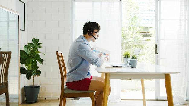 El hombre de negocios asiático vestido con camisa y pantalones cortos usa la computadora portátil para hablar con sus colegas en una videollamada mientras trabaja desde casa en la sala de estar. autoaislamiento, distanciamiento social, cuarentena para la prevención del coronavirus.