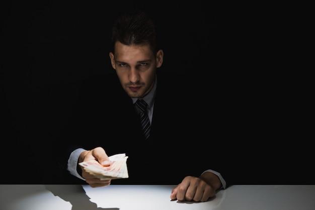 Hombre de negocios astuto engañoso dando dinero en la oscuridad