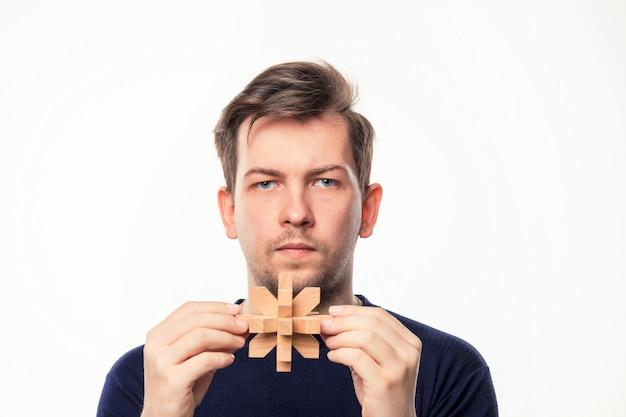 Hombre de negocios atractivo de 25 años que parece confundido con rompecabezas de madera.