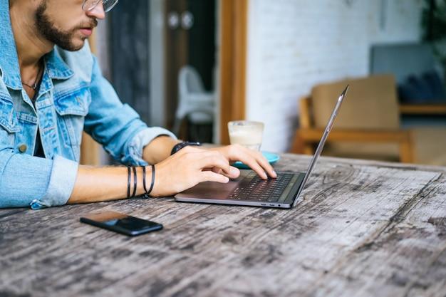 El hombre de negocios atractivo joven en un café trabaja para una computadora portátil, bebe café.