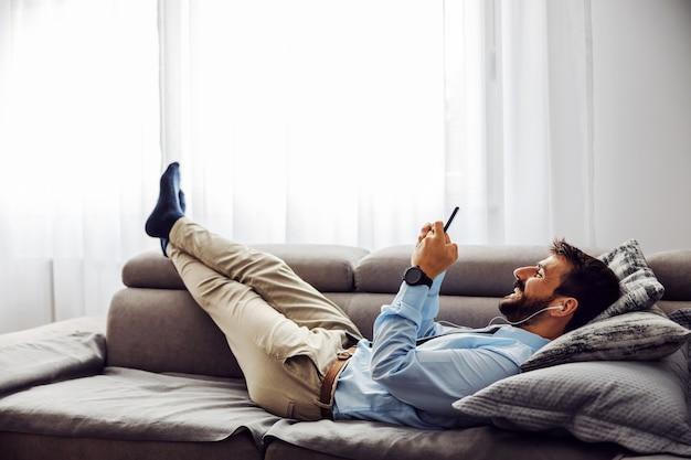 Hombre de negocios atractivo joven que miente en el sofá en casa, relajándose y usando el teléfono inteligente.