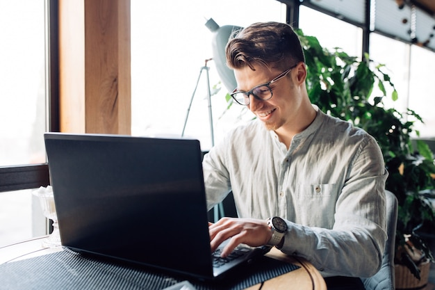 Hombre de negocios atractivo en lentes que trabaja en la computadora portátil, escribiendo, pasando tiempo en el café.