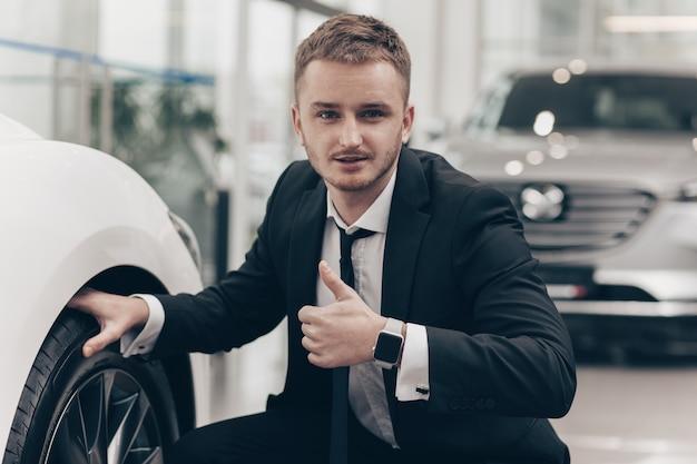 Hombre de negocios atractivo que compra un automóvil nuevo en el concesionario