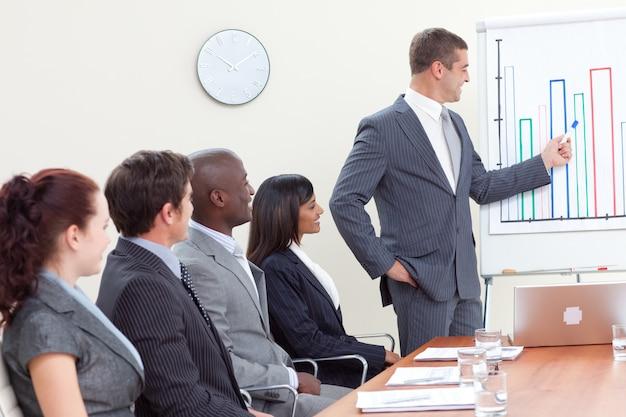 Hombre de negocios atractivo que informa a cifras de ventas