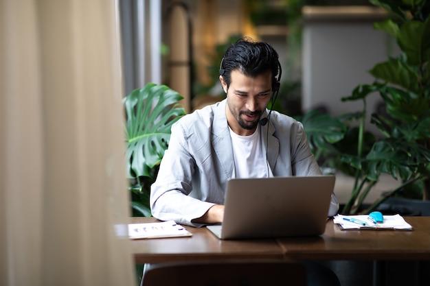 Hombre de negocios atractivo en trajes y auriculares sonriendo mientras trabaja en la computadora de escritorio en el escritorio de la oficina moderna. asistente de servicio al cliente que trabaja en la oficina. auriculares voip helpdesk