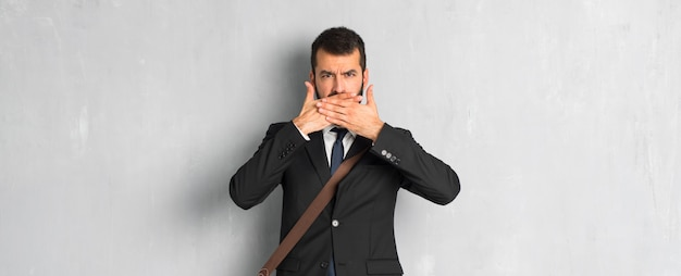 Hombre de negocios con barba cubriéndose la boca con las manos por decir algo inapropiado.