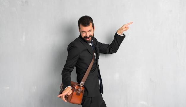 Un hombre de negocios con barba disfruta del baile mientras escucha música en una fiesta