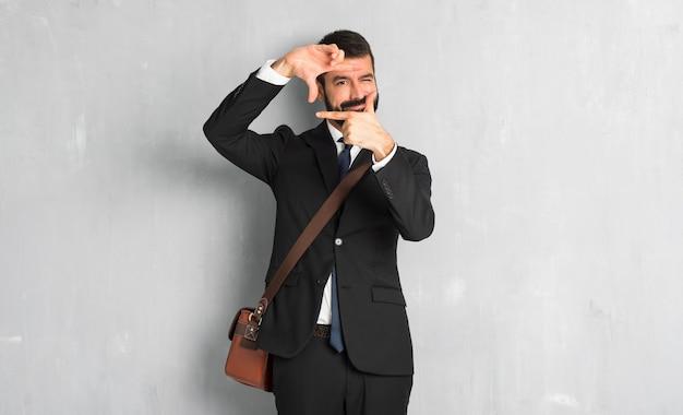 Hombre de negocios con barba enfocando cara. símbolo de encuadre