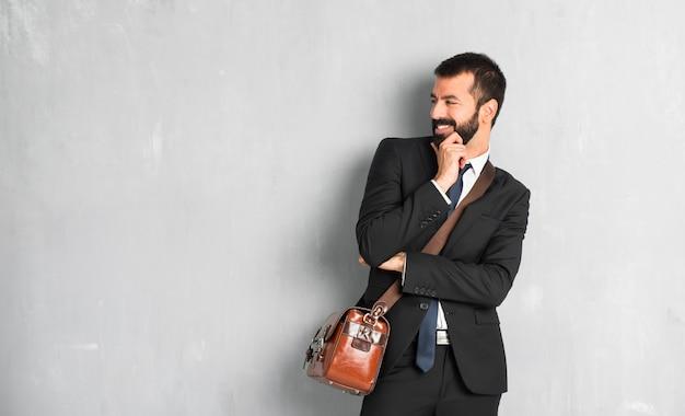 Hombre de negocios con barba mirando hacia un lado con la mano en la barbilla