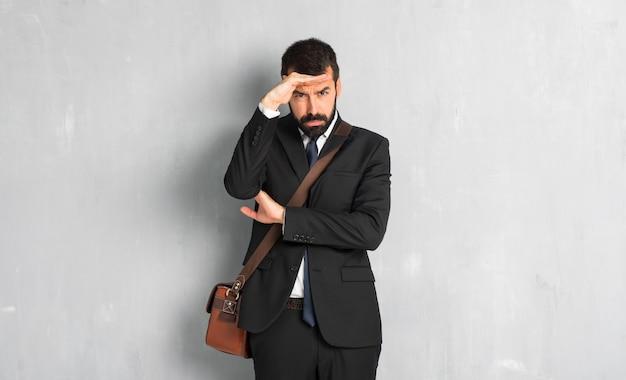 Hombre de negocios con barba mirando lejos con la mano para mirar algo