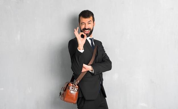Hombre de negocios con la barba que muestra la muestra aceptable mientras que guiña un ojo