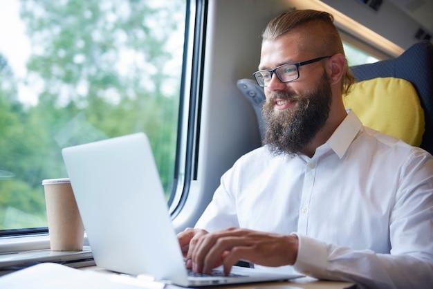 Hombre de negocios con barba trabajando durante el viaje