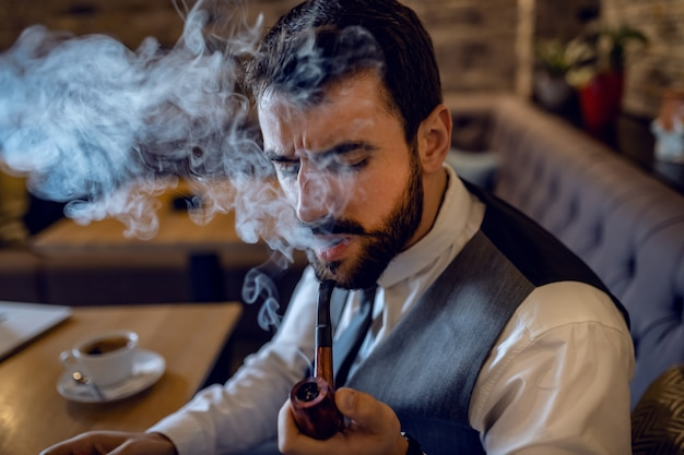 Hombre de negocios barbudo caucásico sofisticado en traje sentado en la cafetería y fumar tabaco de pipa.