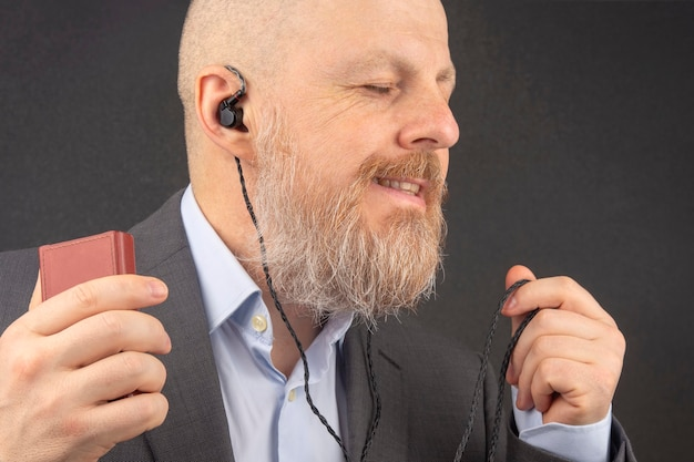 Hombre de negocios barbudo disfruta escuchando su música favorita desde un reproductor de audio con pequeños auriculares.