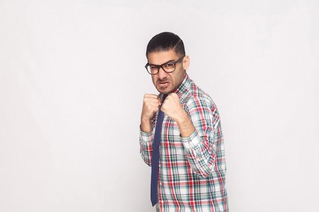 Hombre de negocios barbudo enojado en camisa a cuadros colorida, corbata azul y anteojos negros de pie y mirando a cámara con rostro agresivo y puño. foto de estudio en interiores, aislado sobre fondo gris claro