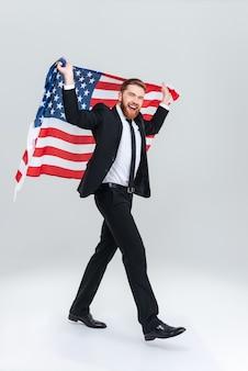 Hombre de negocios barbudo feliz de longitud completa en traje negro sosteniendo la bandera de estados unidos desde la parte posterior. vista lateral. fondo gris aislado