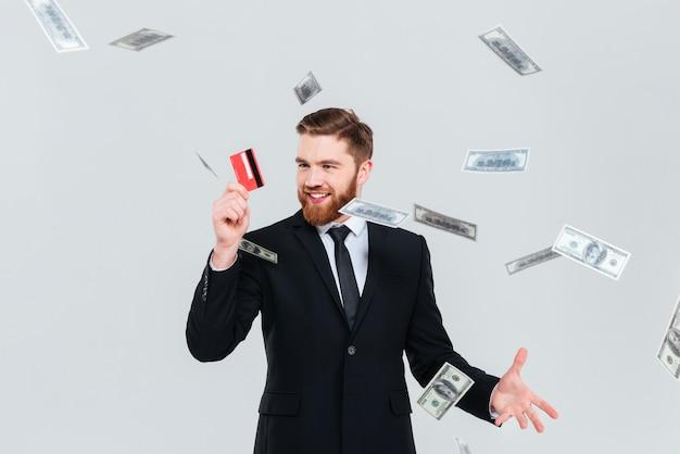 Hombre de negocios barbudo feliz en traje negro con tarjeta de crédito y dinero cayendo. fondo gris aislado