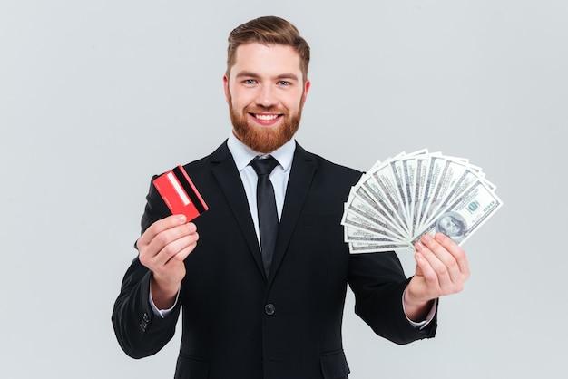 Hombre de negocios barbudo feliz en traje negro con tarjeta de crédito y dinero en las manos. fondo gris aislado