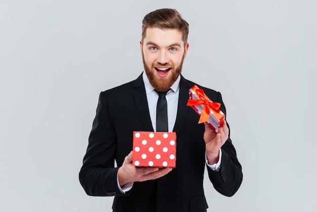 Hombre de negocios barbudo feliz en traje de regalo de apertura