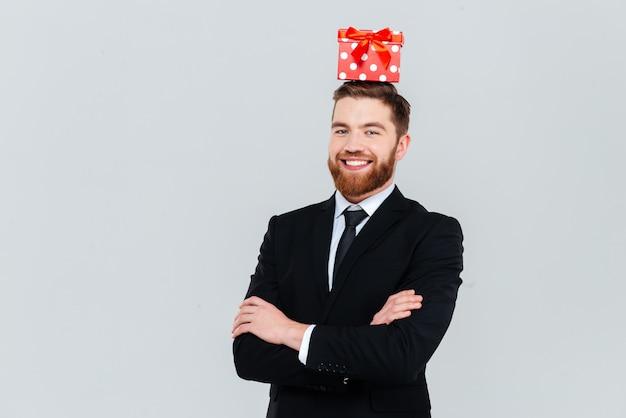 Hombre de negocios barbudo feliz en traje con regalo en la cabeza y los brazos cruzados