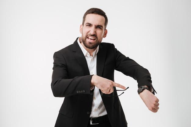 Hombre de negocios barbudo joven enojado que muestra su reloj.