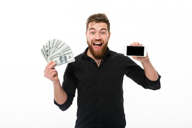Hombre de negocios barbudo satisfecho sorprendido en camisa con dinero