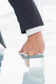 Hombre de negocios bien vestido con el puño cerrado en el escritorio de oficina