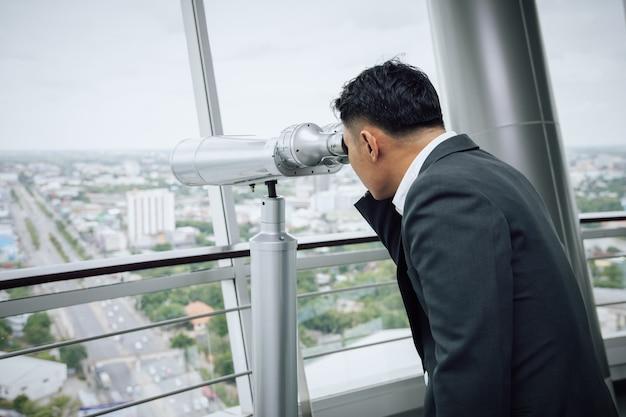 Hombre de negocios con binoculares en la parte superior del edificio en busca del concepto de oportunidad dorada