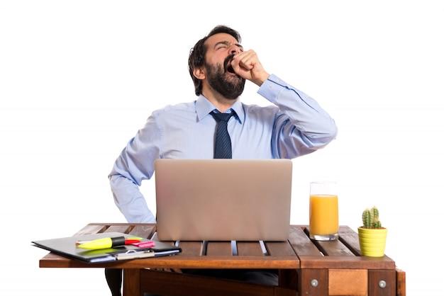 Hombre de negocios bostezando en su oficina